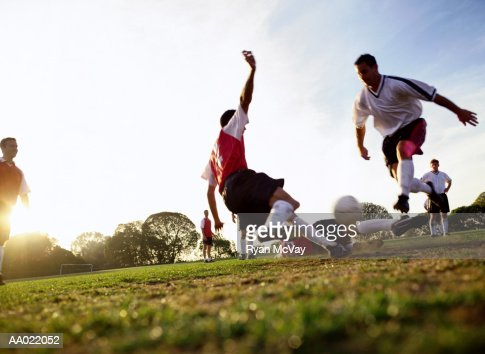 Soccer players tackling for ball, ground view : Photo