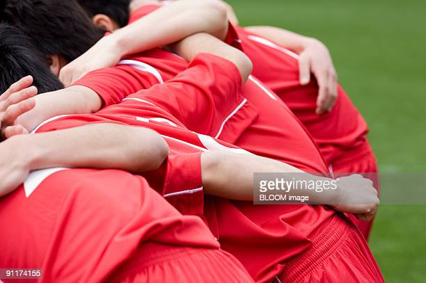 Soccer players with arms around each other