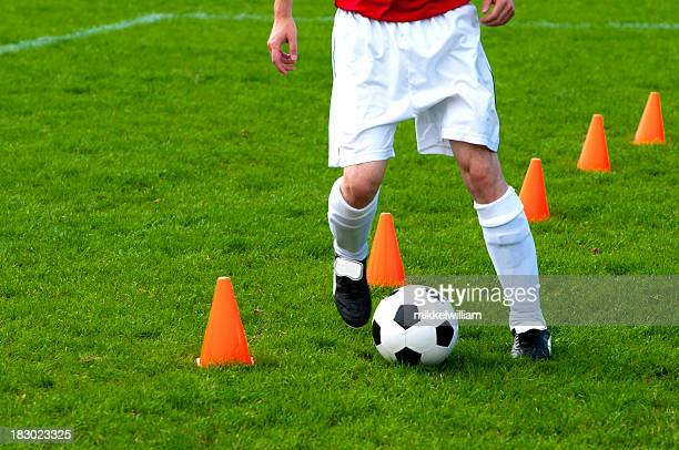 Fußball Trainingsübungen mit Fußball-Spieler läuft mit football