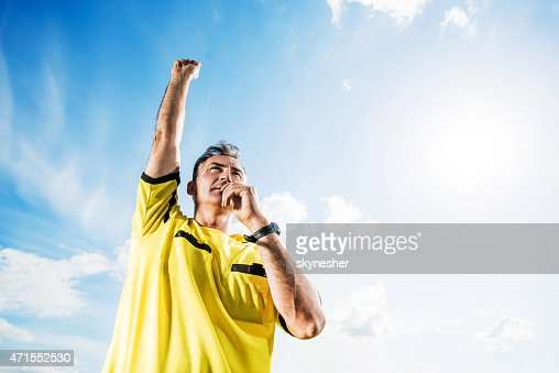 Soccer referee blowing his whistle against the sky.