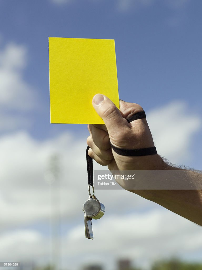 A soccer referee holding a yellow card