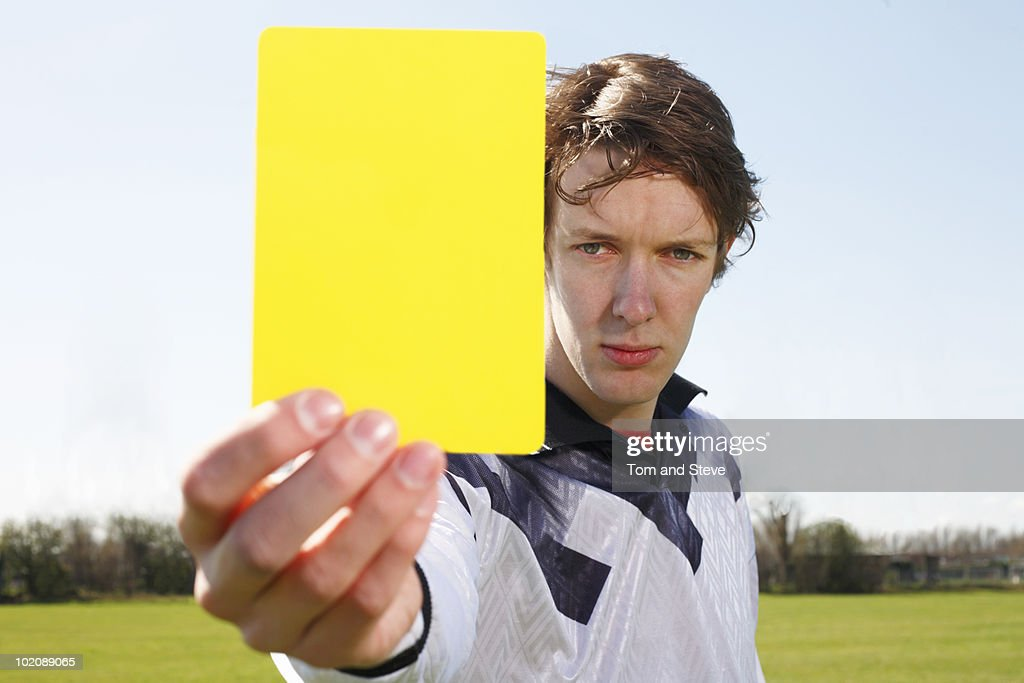 Soccer Referee Holding up Yellow Card