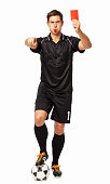 Full length portrait of soccer referee with ball showing red card while pointing over white background. Vertical shot.