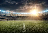soccer stadium with green grass and illumination on a sunset