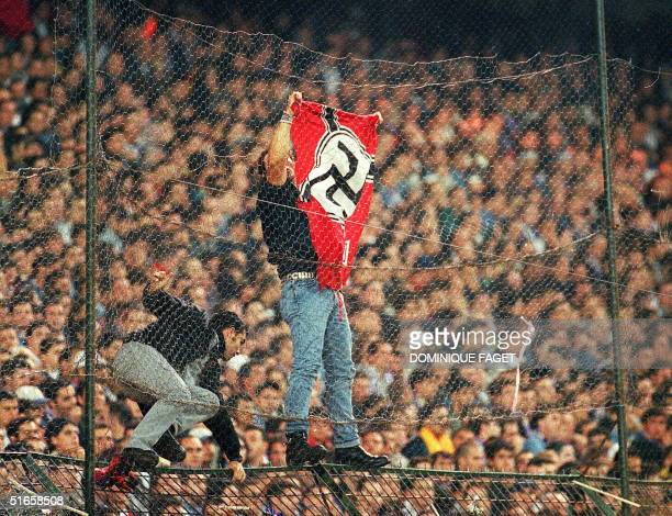 A soccer supporter attaches a Nazi flag to a crowd barrier during a Spanish first division match between Real Madrid and Barcelona in Bernabeu...