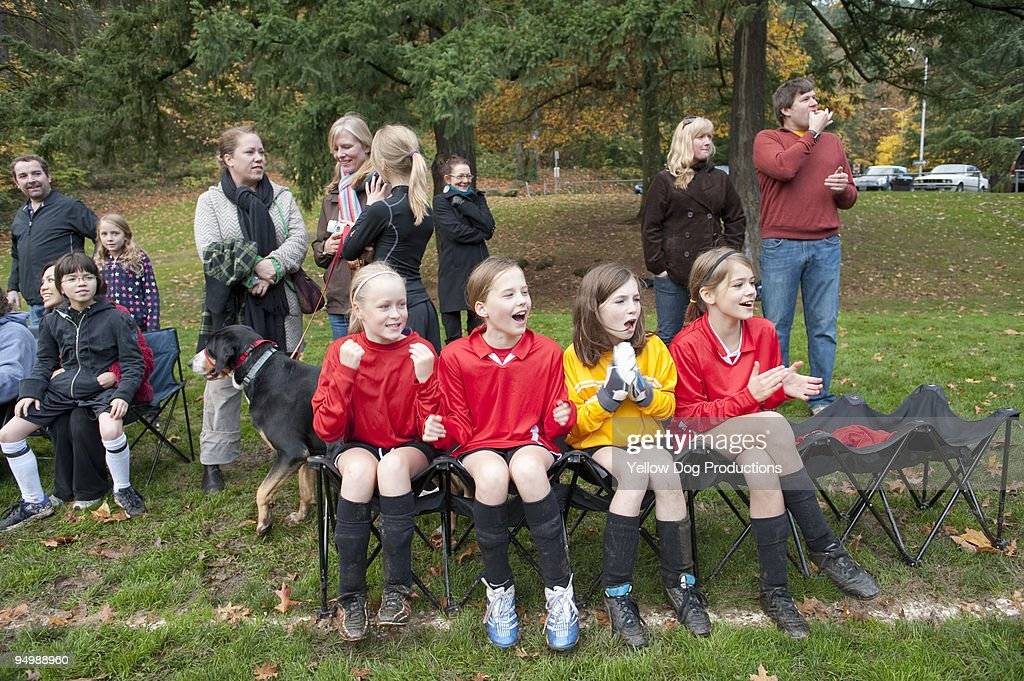 Soccer team and spectators cheering on sidelines  : Stock Photo
