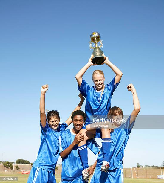 Soccer team holding up winning trophy with pride. Cape Town, Western Cape Province, South Africa