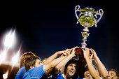 Soccer Team Raising Trophy