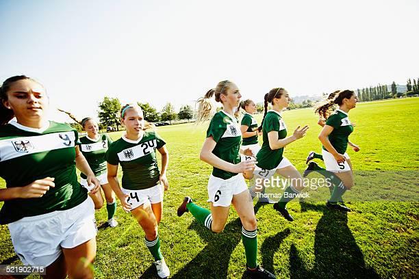 Soccer teammates running on grass field warming up