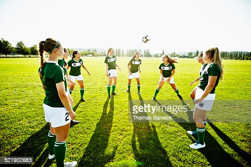 Soccer teammates standing in circle heading ball