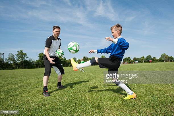 Soccer trainer teaching young player helping
