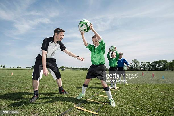 Soccer trainer teaching young players