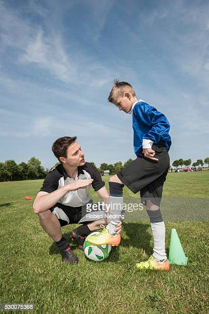 Soccer trainer testing young player helping