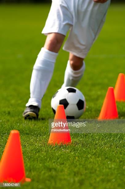 FUSSBALLTRAINING mit Fußball und roten Hütchen auf dem Feld