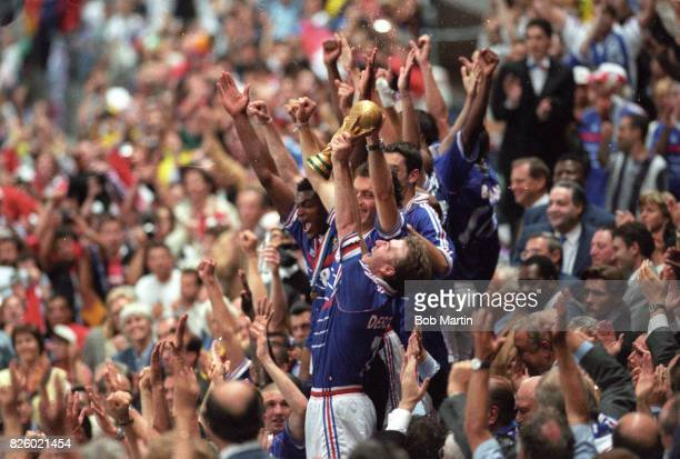 World Cup France Didier Deschamps victorious holding up trophy with teammates after winning game vs Brazil at Stade de France SaintDenis France...