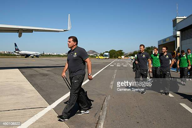 Socceroos coach Ange Postecoglou and Australian players walk along the tarmac to their charter flight to Salvador at Vitoria Airport on June 5 2014...