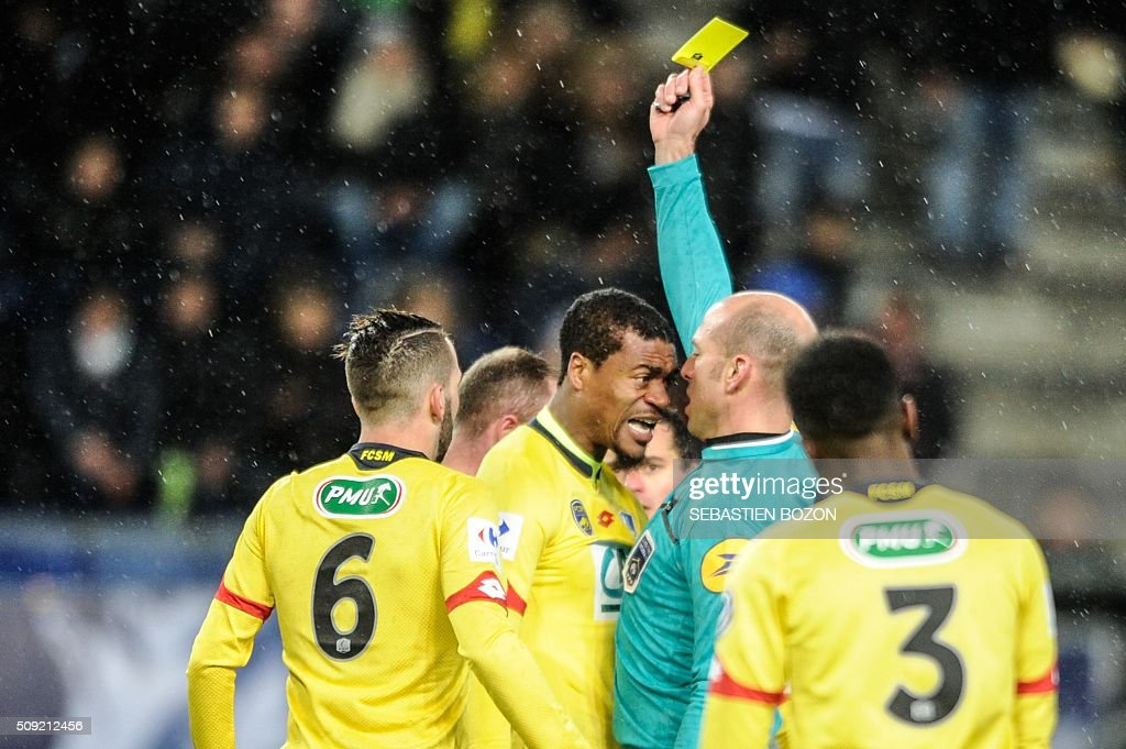 Sochaux' Cameroonese defender Adolphe Teikeu (C) reacts as he receives a yellow card from the referee, Bartolomeu Varela Teles, during the French cup round of 8 football match between Sochaux (FCSM) and Monaco (ASM) at the Auguste Bonal Stadium in Montbeliard, on February 9, 2016. / AFP / SEBASTIEN BOZON