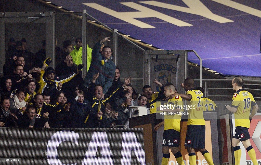 Sochaux' French forward Giovanni Sio (2nd R) is congratulated by his teammates and supporters after scoring a goal during the French L1 football match Lyon vs Sochaux on March 31, 2013 at the Gerland stadium in Lyon, southeastern France.