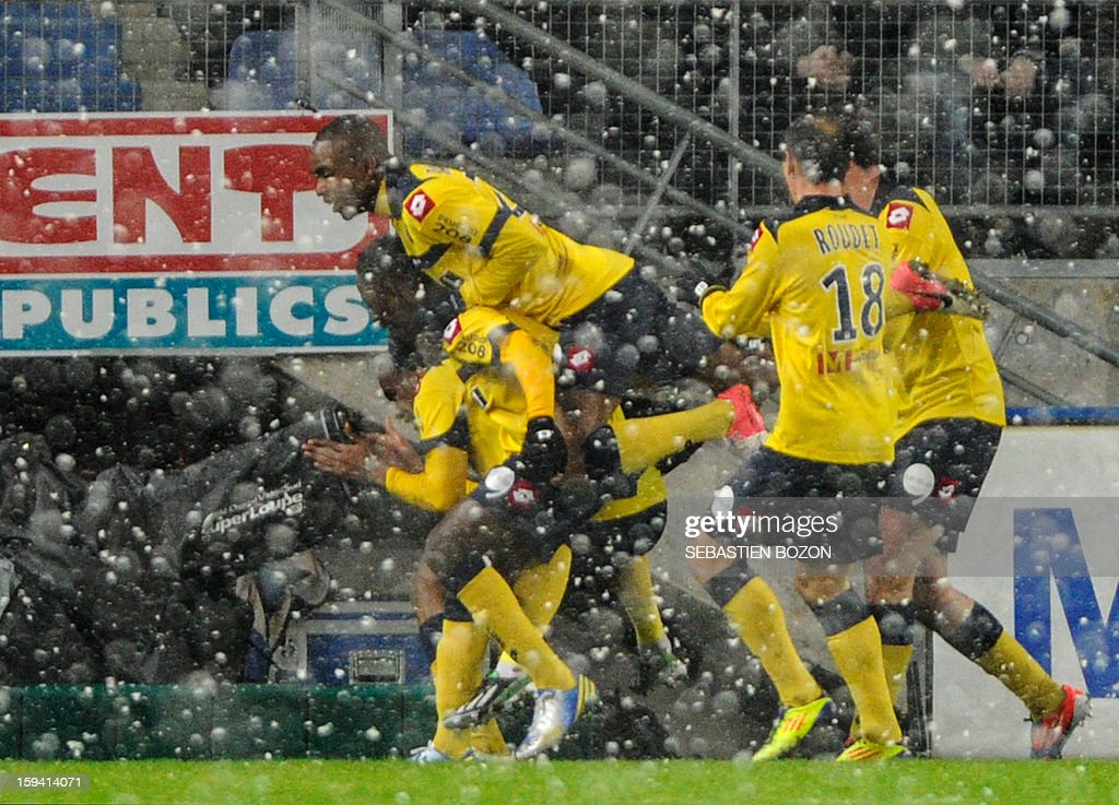 Sochaux' French forward Sloan Privat (hidden) is congratulated after scoring a goal during the French L1 football match Sochaux (FCSM) versus Marseille (OM) at the August Bonal Stadium in Montbeliard, on January 13, 2013.