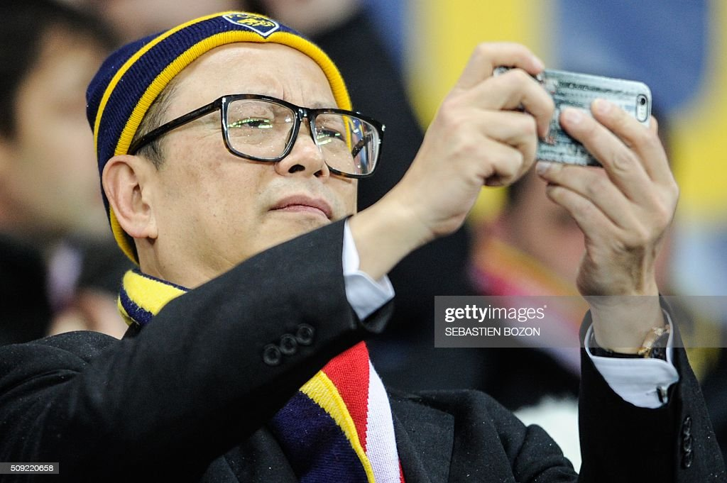Sochaux' owner, Li Wing-Sang takes a picture with his phone before the French cup round of 8 football match between Sochaux (FCSM) and Monaco (ASM) at the Auguste Bonal Stadium in Montbeliard, on February 9, 2016. / AFP / SEBASTIEN BOZON