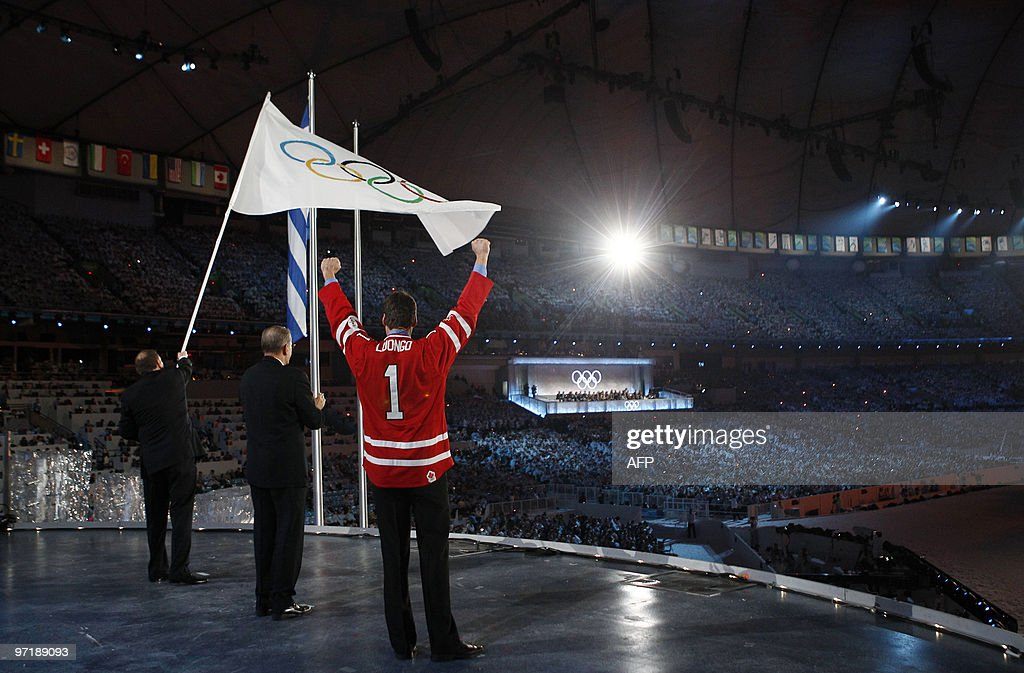 Sochi Mayor Anatoly Pakhomov (L) waves the Olympic flag next to International Olympic Committee (IOC) President Jacques Rogge (C) and Vancouver Mayor Gregor Robertson during the closing ceremony of the Vancouver 2010 Winter Olympics, February 28, 2010. AFP PHOTO POOL / JIM YOUNG