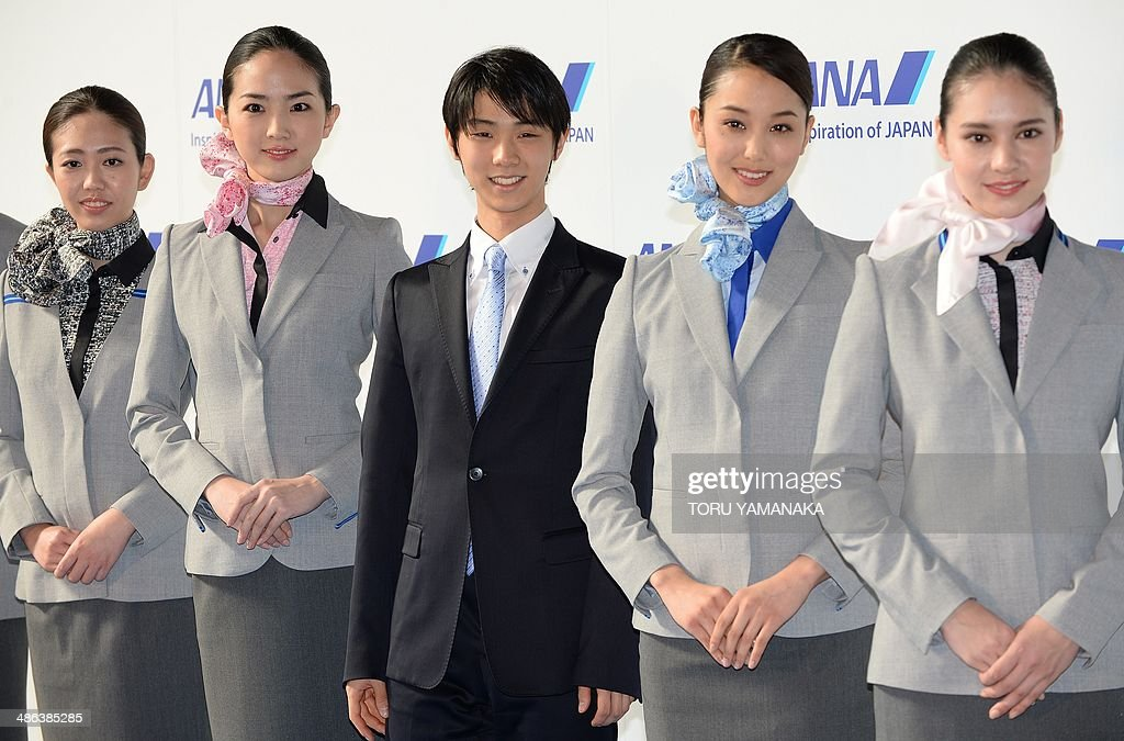 Sochi Olympic filgure skating gold medalist Yuzuru Hanyu (C) introduces the new uniforms designed by US desiner Prabal Gurung during a press conference at its hanger of Haneda Airport in Tokyo on April 24, 2014. The Japanese airline will renew all uniforms of some 13,000 cabin attendants and ground staffs. AFP PHOTO/Toru YAMANAKA