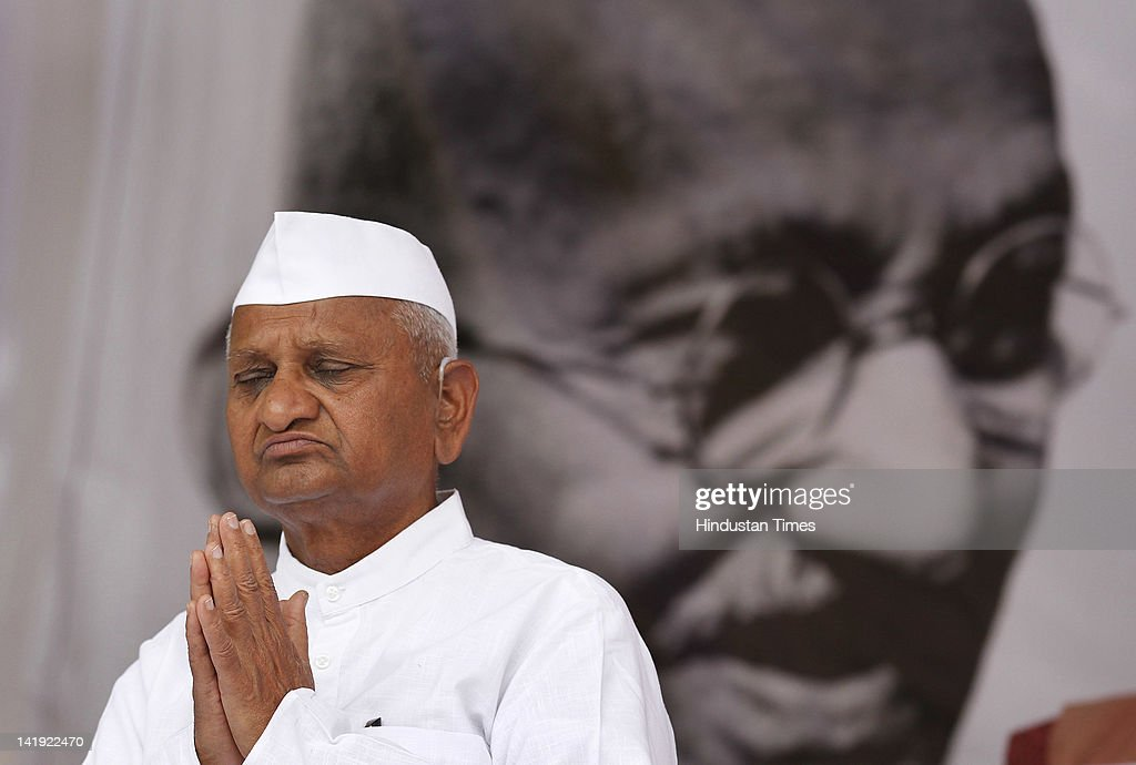 Social activist <a gi-track='captionPersonalityLinkClicked' href=/galleries/search?phrase=Anna+Hazare&family=editorial&specificpeople=5963003 ng-click='$event.stopPropagation()'>Anna Hazare</a> sits in front of portrait of Mahatma Gandhi during his day long fast at Jantar Mantar on March 25, 2012 in New Delhi, India. Team Anna members Manish Shisodia (L) and Kumar Vishwas (R) also seen in the picture. The fast was organized to press for a strong law to protect whistleblowers.