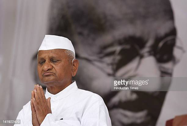 Social activist Anna Hazare sits in front of portrait of Mahatma Gandhi during his day long fast at Jantar Mantar on March 25 2012 in New Delhi India...