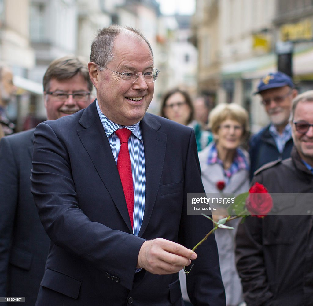 Social Democrats (SPD) chancellor candidate Peer Steinbrueck distributes roses to passers-by while making a campaign appearance on September 20, 2013 in Wiesbaden, Germany. Germany is facing federal elections scheduled for September 22 and a wide spectrum of political parties is vying for votes.