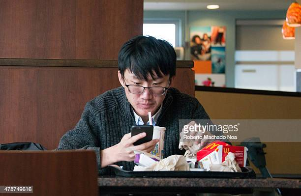 Social disconnection due to mobile devices Asian guy with short hair and glasses sitting eating at McDonalds while texting on his cell phone during...