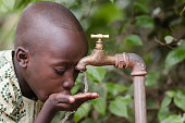 Water scarcity in the world symbol. African boy begging for water. In places like sub-Saharan Africa, time lost to gather water and suffering from water-borne diseases is limiting people's lives.