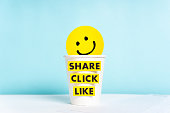 Social media and content marketing concept with happy smiling yellow face over cup paper and share click like words, blue background.
