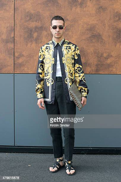Social media consultant Lurzio Cremaschia wears Versace shirt Anatonia trousers Versace shoes Versace sunglasses and Goyard clutch on day 4 of Paris...