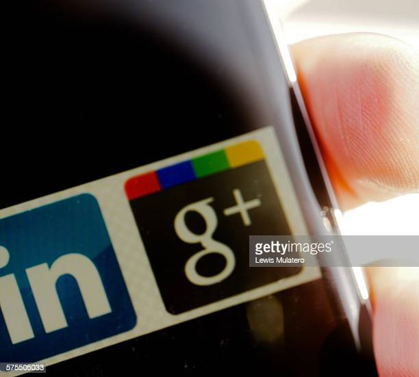 Social media Extreme close up of fingers holding mobile phone with social media network classic icons visible on screen LinkedIn and Google