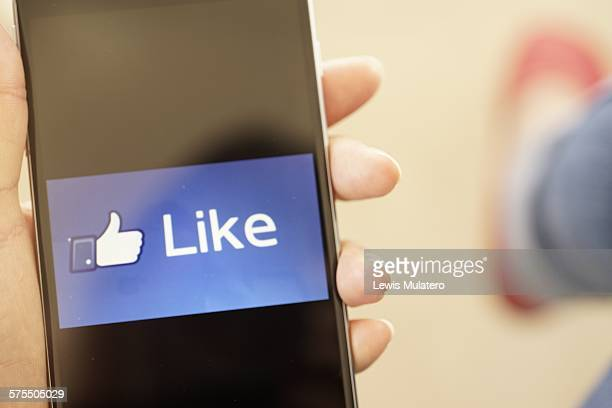 Social media Female hand holding a mobile phone with the word Like and thumbs up showing on phone screen Space for copy