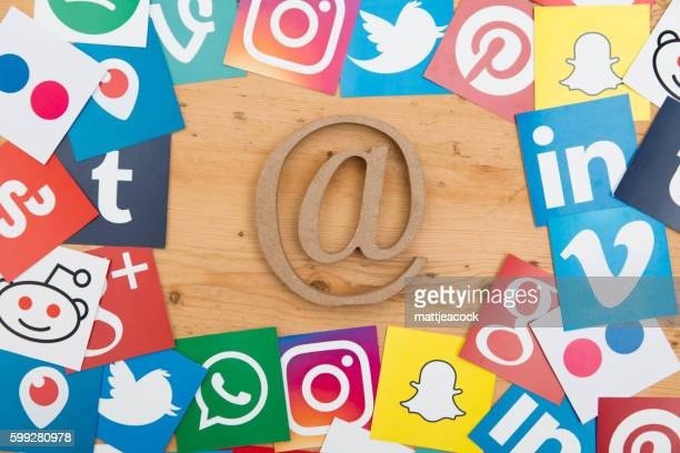 Social media icons and at symbol on a wooden background