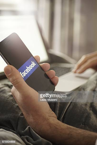 Social media Man laying in bed multi tasking One hand holds a mobile phone with Facebook classic word icon on screen whilst other hand is using...