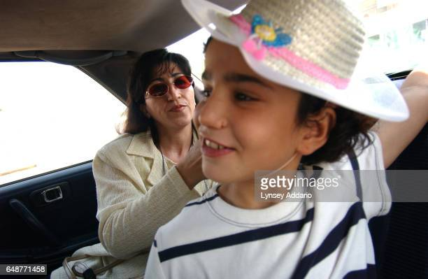 A social worker arranges Sanaria's hat while on their way to visit Sanaria's mother after being placed in an orphanage in Baghdad Iraq August 2003...