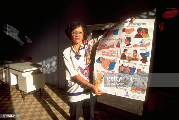 A social worker displays a poster explaining safe sex AIDS and sexually transmitted diseases