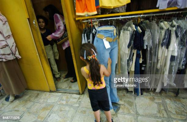 A social worker helps Sanaria in the dressing room while taking her to buy a new outfit before returning to the orphanage in Baghdad Iraq August 2003...