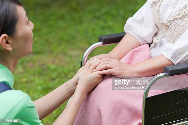 Social Worker Holding Senior Woman's Hands
