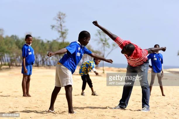 Social worker Isboulah train with children from the Yakaaru Guneye center during a football game in Guediawaye near Dakar on July 19 2017 Senegal's...