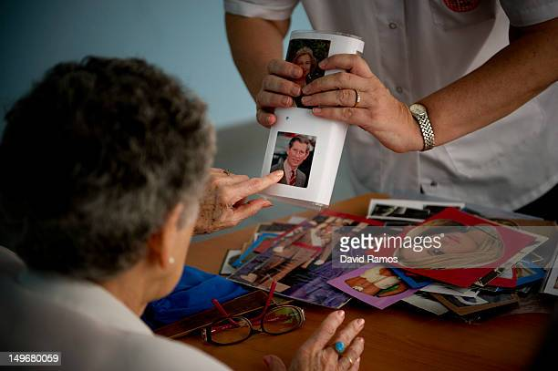 Social worker Nuria Casulleres shows a portrait of Prince Charles Prince of Wales to an elderly woman during a memory activity at the Cuidem La...