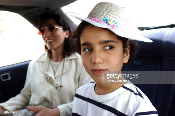 A social worker sits with Sanaria while on their way to visit Sanaria's mother after being placed in an orphanage in Baghdad Iraq August 2003 Sanaria...
