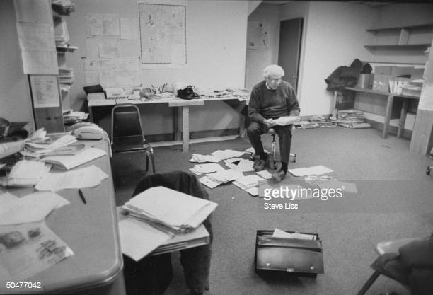 Socialist congressional cand Bernie Sanders reading mail in papercovered campaign office in Burlington