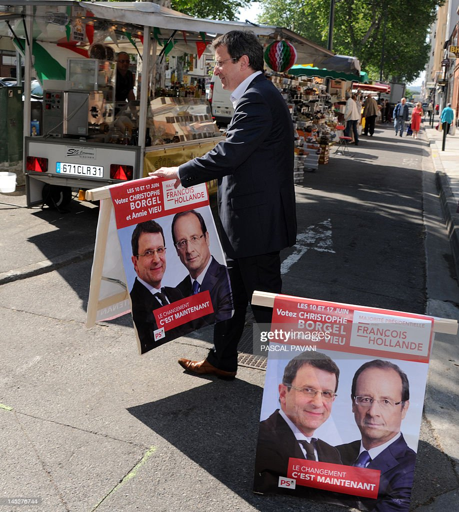 Socialist Party (PS) candidate for the June 2012 French parliamentary election in the 9th constituency of Haute-Garonne department Christophe Borgel sets electoral posters in a street, on May 25, 2012, in Toulouse, southwestern France, as part of his campaign.