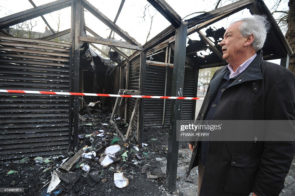 Socialist Party (PS) Mayor Patrick Rimbert looks at a tramway station in Nantes, western France, on February 23, 2014 which was burnt down by protesters opposed to plans to build the Notre-Dames-des-Landes airport for the French city of Nantes. Protesters smashed shop windows on February 22 and hurled paving stones at police, who answered with tear gas and rubber bullets. Tens of thousands of protesters against building the airport on protected swampland swarmed the western city's Petite Hollande square, the latest in a string of demonstrations against the pet project of Prime Minister Jean-Marc Ayrault.