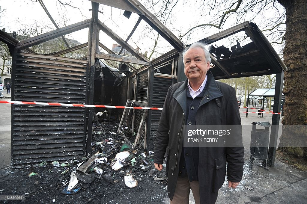 Socialist Party (PS) Mayor Patrick Rimbert stands in front of a tramway station in Nantes, western France, on February 23, 2014 which was burnt down by protesters opposed to plans to build the Notre-Dames-des-Landes airport for the French city of Nantes. Protesters smashed shop windows on February 22 and hurled paving stones at police, who answered with tear gas and rubber bullets. Tens of thousands of protesters against building the airport on protected swampland swarmed the western city's Petite Hollande square, the latest in a string of demonstrations against the pet project of Prime Minister Jean-Marc Ayrault.