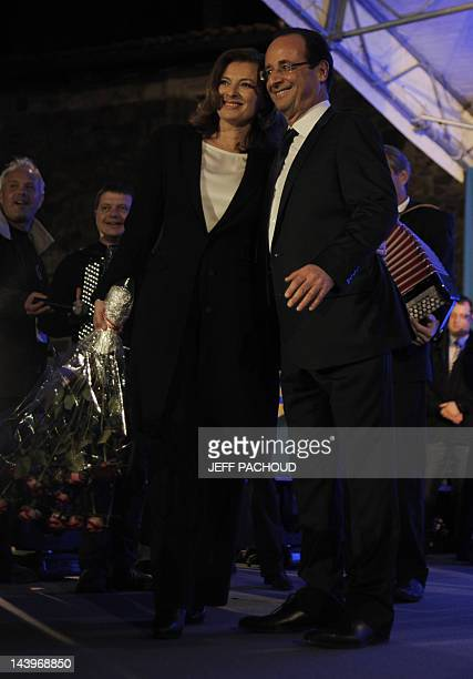 Socialist Party newly elected president Francois Hollande poses flanked by his companion Valerie Trierweiler after given a speech after the results...