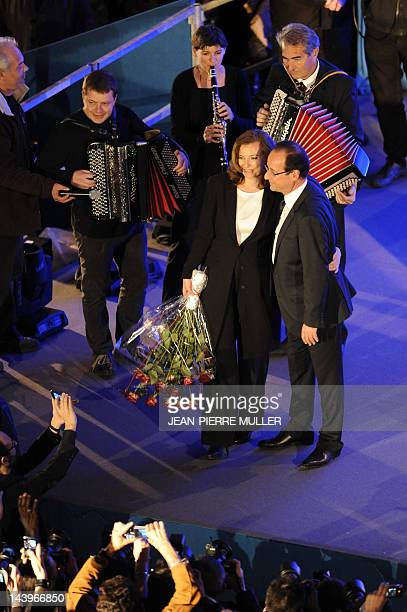 Socialist Party newly elected president Francois Hollande waves near his companion Valerie Trierweiler after winning the second round of the...